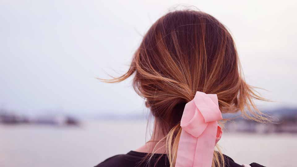Woman with pink hair bow.
