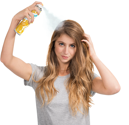 Woman spraying dry shampoo bottle.